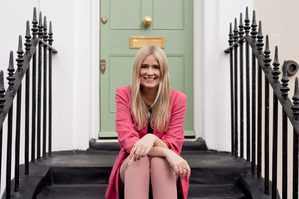 blonde woman smiling in front of green door wearing pink suit London personal branding session