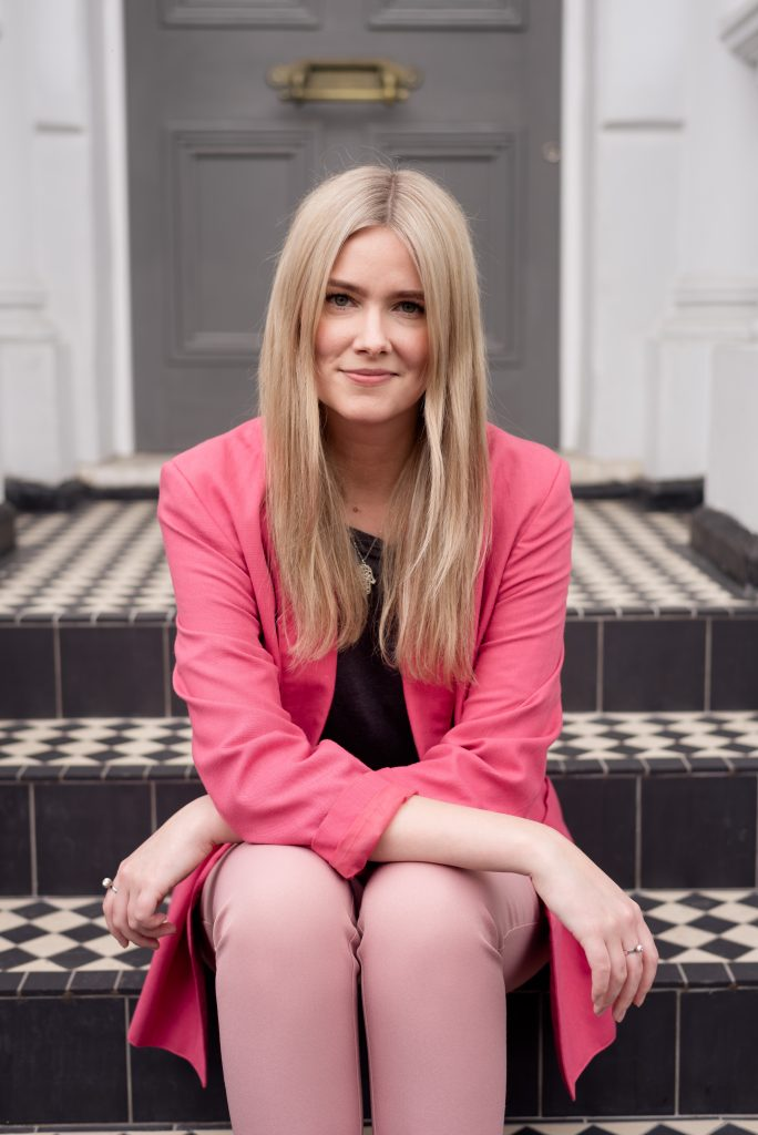 blonde lady smiling on checkered steps in Notting Hill wearing pink suit
