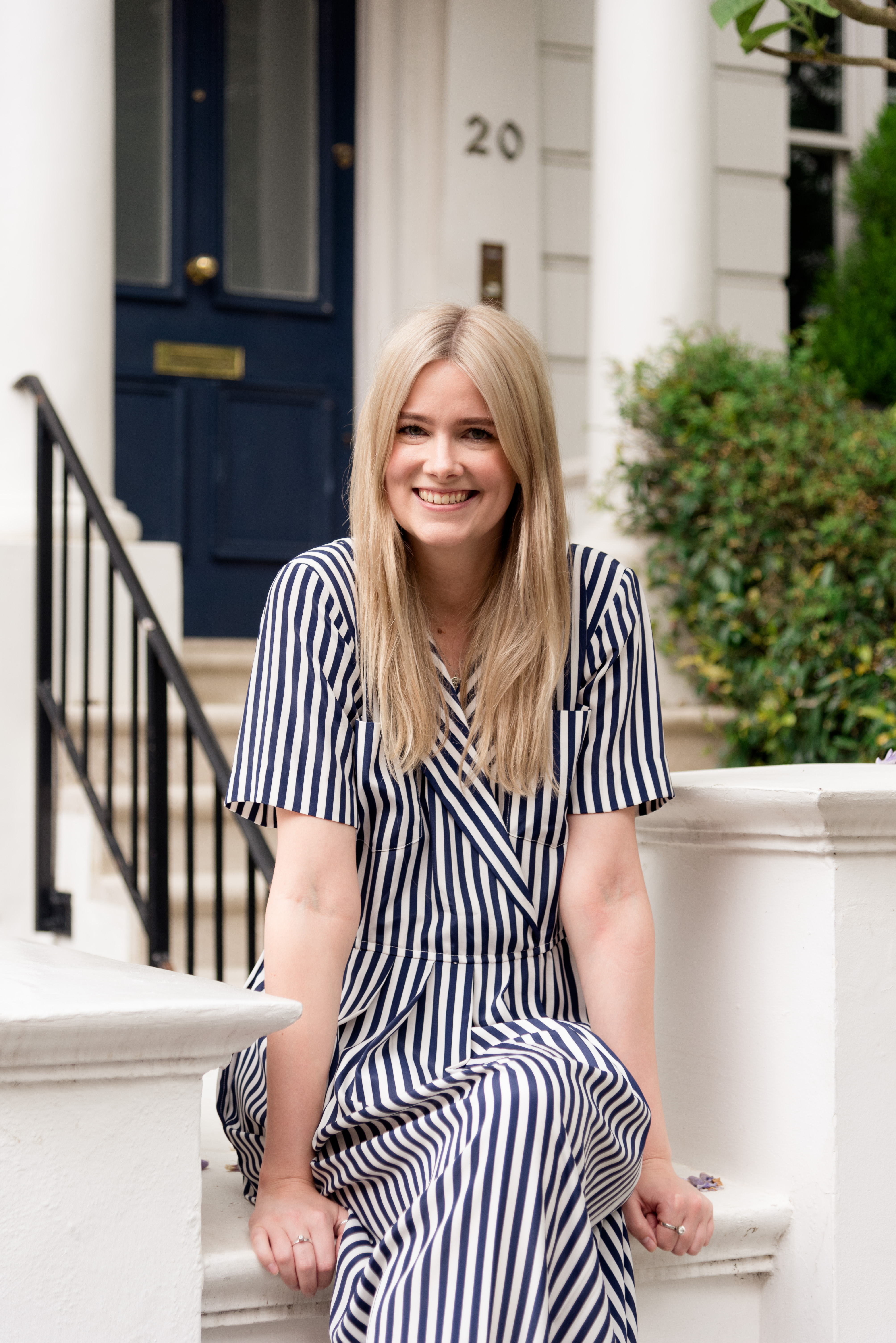 blonde lady sitting on a wall in stripy jumpsuit
