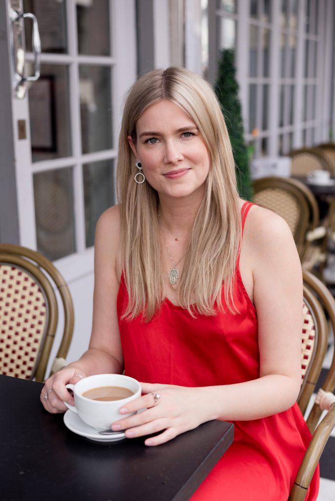 blonde lady wearing red dress drinking tea