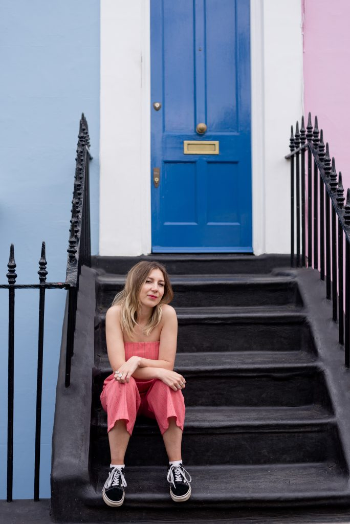 brunette wearing pink jumpsuit sitting on steps in front of blue house in Notting Hill
