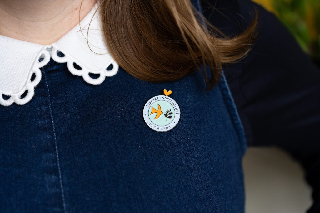 Just a card enamel pin modelled by Kate Marsden