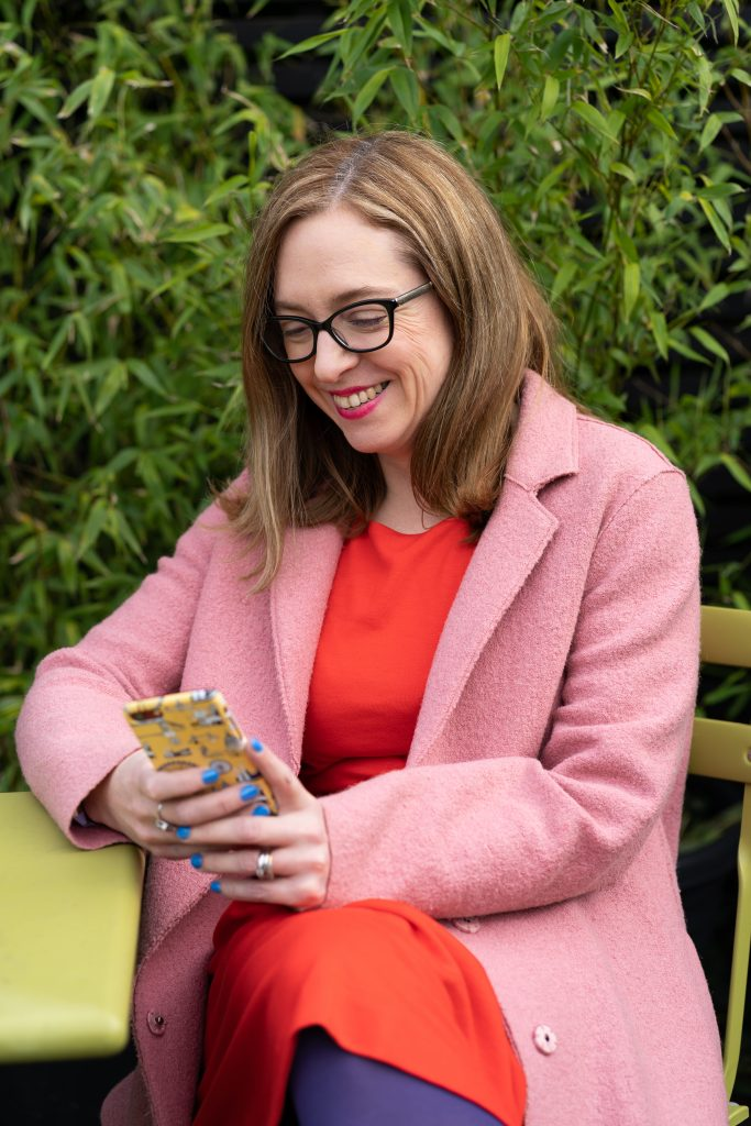 Kate Marsden textile designer sitting outside on green garden furniture looking at her phone