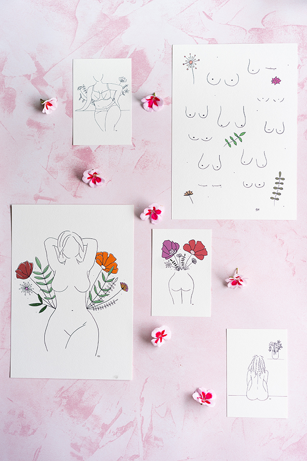 flat lay of illustrators prints on pink backdrop