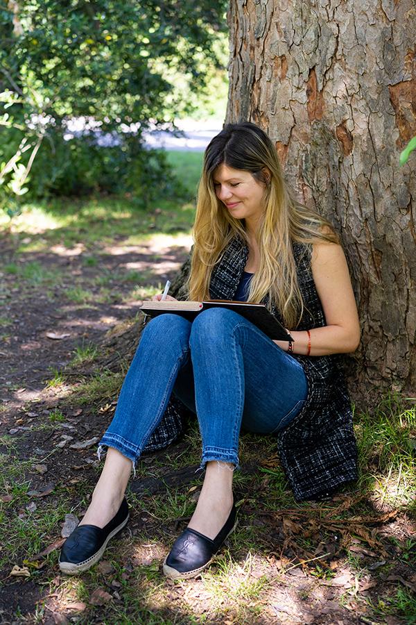 woman writing in journal in Battersea Park