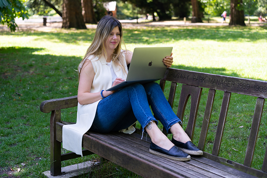 woman on her laptop sitting on a bench in Battersea Park