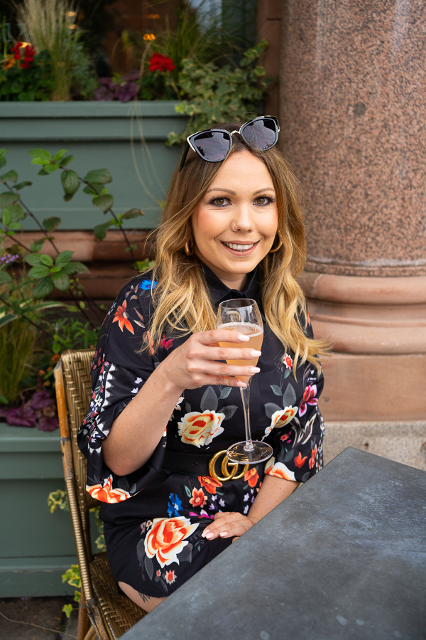 woman in beautiful dress enjoying a drink outside The Ivy Wimbledon