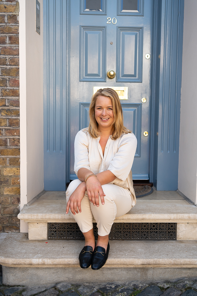 blonde lady sitting on steps in front of blue door