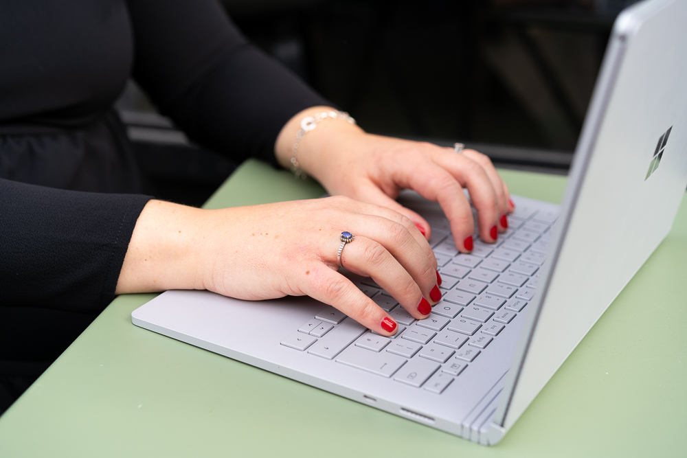 close up shot of hands typing on laptop in London cafe